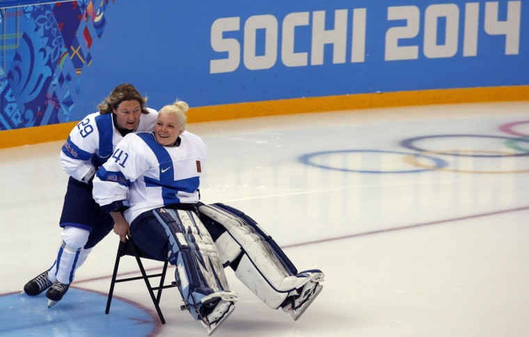 Finland's Karoliina Rantamaki pushes teammate Noora Raty on a chair across the ice after gathering for a team photo before a training session at the Shayba Arena in preparation for the 2014 Sochi Winter Olympics. (REUTERS/Grigory Dukor)