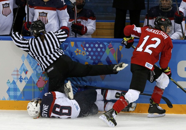 An official falls on Team USA's Kendall Coyne after she collided with Canada's Meaghan Mikkelson during the first period of their women's ice hockey game at the 2014 Sochi Winter Olympics, February 12, 2014. REUTERS/Grigory Dukor