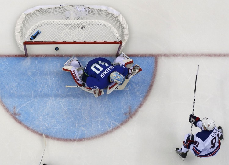 Team USA's Phil Kessel scores a goal on Slovenia's goalie Luka Gracnar during the first period of their men's preliminary round ice hockey game at the 2014 Sochi Winter Olympics, February 16, 2014. (Brian Snyder/Reuters)
