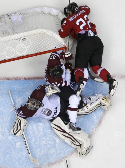 Switzerland's Nino Niederreiter (R) crashes into Latvia's goalie Edgars Masalskis and Oskars Bartulis during the third period of their men's qualification round ice hockey game at the 2014 Sochi Winter Olympic Games, February 18, 2014. REUTERS/Mark Blinch