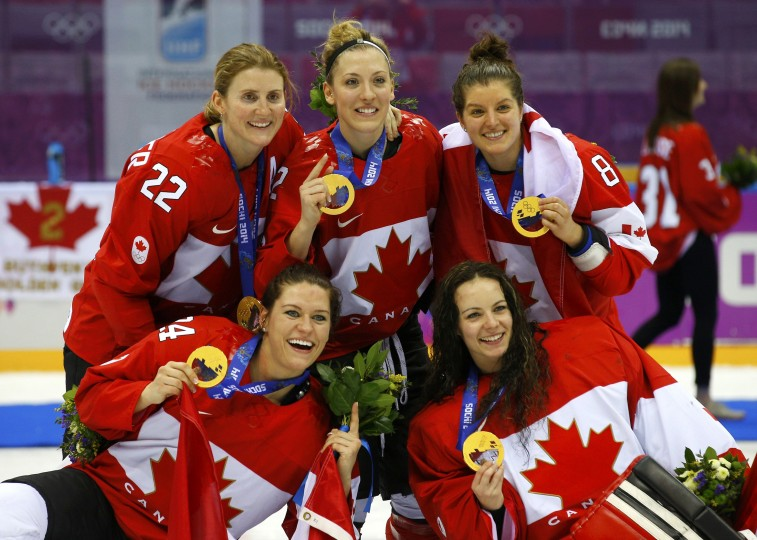 Canada's Hayley Wickenheiser (rear, L), Meghan Agosta-Marciano (rear, C), Laura Fortino (rear, R), Natalie Spooner (front, L) and goalie Shannon Szabados pose with their gold medals after their team defeated Team USA in overtime in the women's ice hockey final game at the 2014 Sochi Winter Olympics, February 20, 2014. (REUTERS/Brian Snyder)