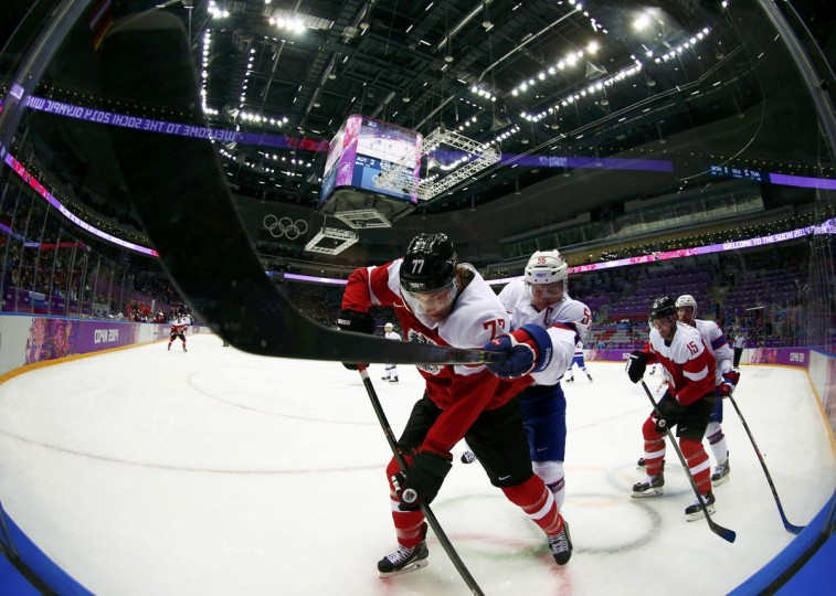 Austria's Brian Lebler (left) and Norway's Ole-Kristian Tollefsen fight for the puck during the second period of their men's preliminary round hockey game at the Sochi 2014 Winter Olympic Games February 16, 2014. (Mark Blinch/Reuters)