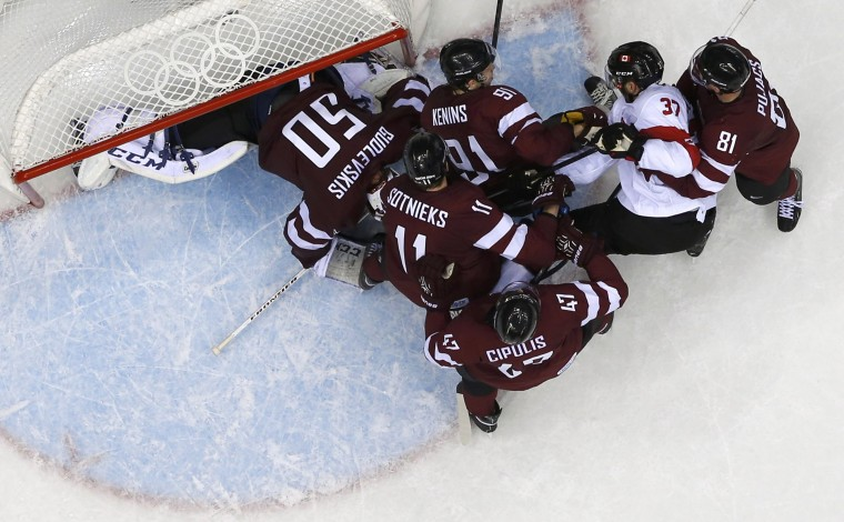 Canada's Patrice Bergeron (37) is blocked from scoring by Latvia's goalie Kristers Gudlevskis (50) and several defenders in the third period of their men's quarter-finals ice hockey game at the 2014 Sochi Winter Olympic Games, February 19, 2014. (REUTERS/Mark Blinch)