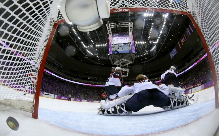 A shot by Canada's Marie-Philip Poulin enters the net to score the winning goal in overtime past Team USA's goalie Jessie Vetter during their women's ice hockey gold medal game at the Sochi 2014 Winter Olympic Games February 20, 2014. (REUTERS/Martin Rose/Pool)