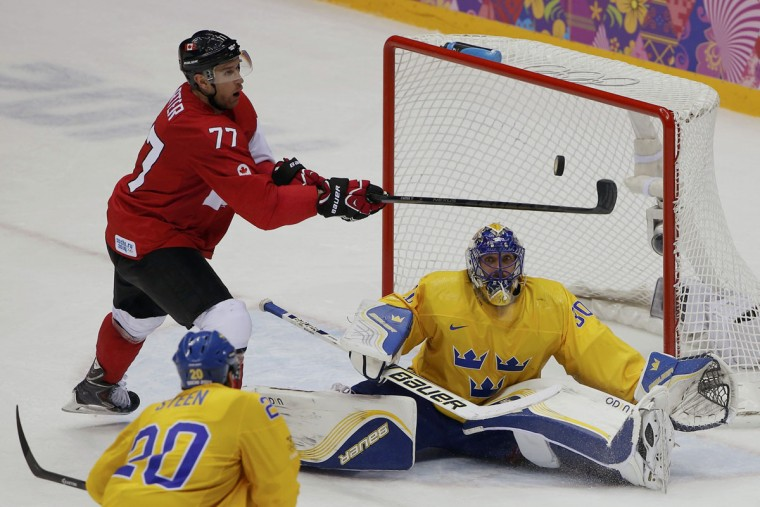 Canada's Jeff Carter tries to hit a bouncing puck past goalie Henrik Lundqvist as Sweden's Alexander Steen looks on. (REUTERS/Jim Young)