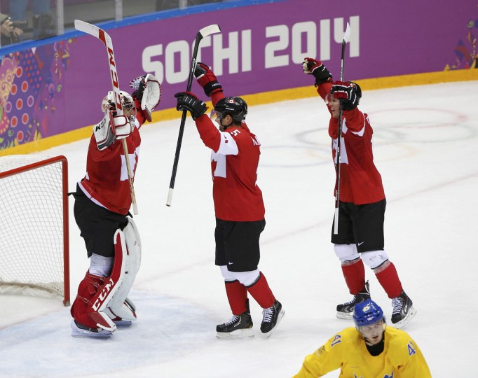 Canada goalie Carey Price and teammates Dan Hamhuis (center) and Jonathan Toews celebrate after defeating Sweden in the men's ice hockey gold medal game at the 2014 Sochi Winter Olympic Games. (REUTERS/Jim Young)