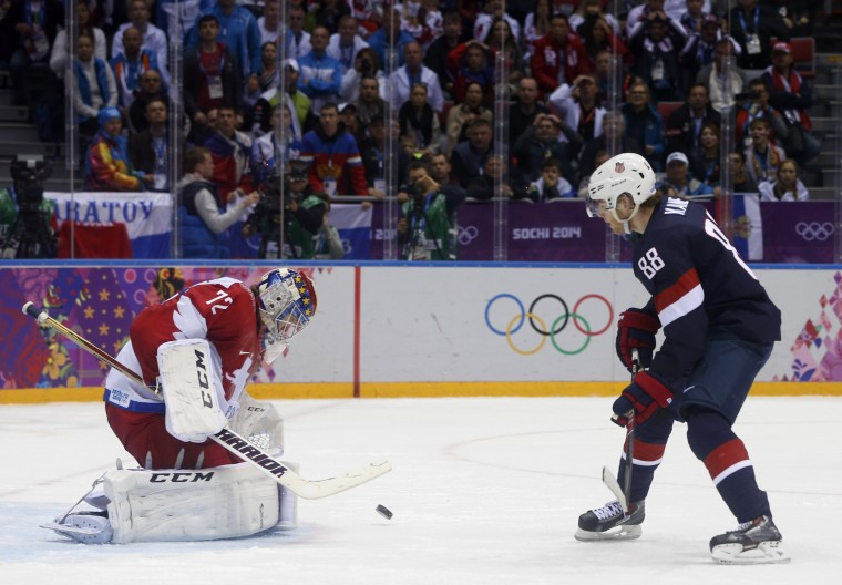 Russia's goalie Sergei Bobrovski (L) makes a breakaway save on Team USA's Patrick Kane during the overtime period of their men's preliminary round ice hockey game at the Sochi 2014 Winter Olympic Games February 15, 2014. REUTERS/Gary Hershorn
