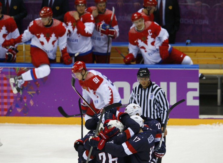 Members of Team USA (front) celebrate after defeating Russia in a shootout during their men's preliminary round ice hockey game at the Sochi 2014 Winter Olympic Games February 15, 2014. REUTERS/Brian Snyder