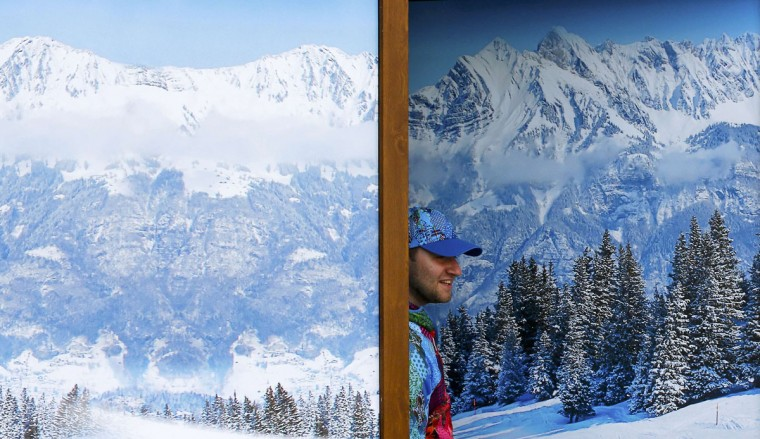 A volunteer looks out of a window as he watches the preparation for the welcoming ceremony for India's team, in the Olympic athlete's village which stands on a mountain plateau in Rosa Khutor, during the 2014 Winter Olympic Games February 16, 2014. India completed its return to the Olympic family on Sunday when its flag was hoisted at the Sochi Games, five days after the International Olympic Committee lifted its suspension on the Southeast Asian nation. (Shamil Zhumatov/Reuters)