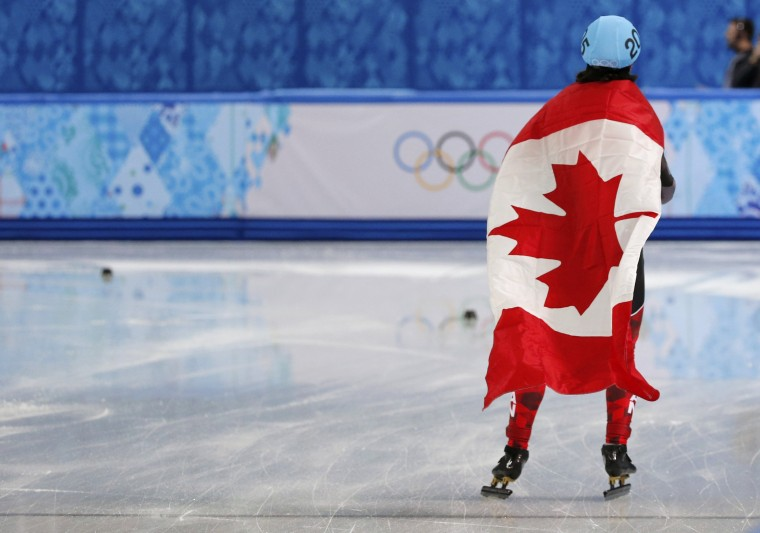 Charles Hamelin of Canada wears his country's flag as he celebrates his victory in the men's 1,500-meter short track speedskating finals event at the 2014 Sochi Winter Olympics, February 10, 2014. (Alexander Demianchuk/Reuters)
