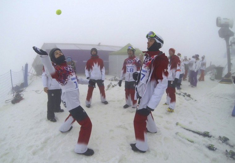 Canada's Christopher Robanske and compatriot Kevin Hill play with a tennis ball as they wait for the start of the men's snowboarding cross qualification round during a delay because of the fog at the 2014 Sochi Winter Olympic Games in Rosa Khutor, February 17, 2014. Fog and drizzle shrouded the course as practice runs were due to begin. (Mike Blake/Reuters)