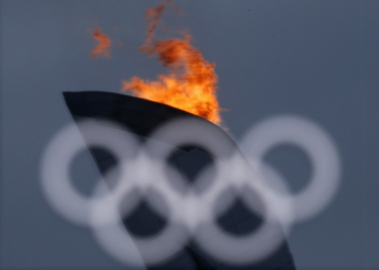 The Olympic flame is reflected in a window at the Olympics Park during the Sochi 2014 Winter Olympics February 11, 2014. (REUTERS/Alexander Demianchuk)