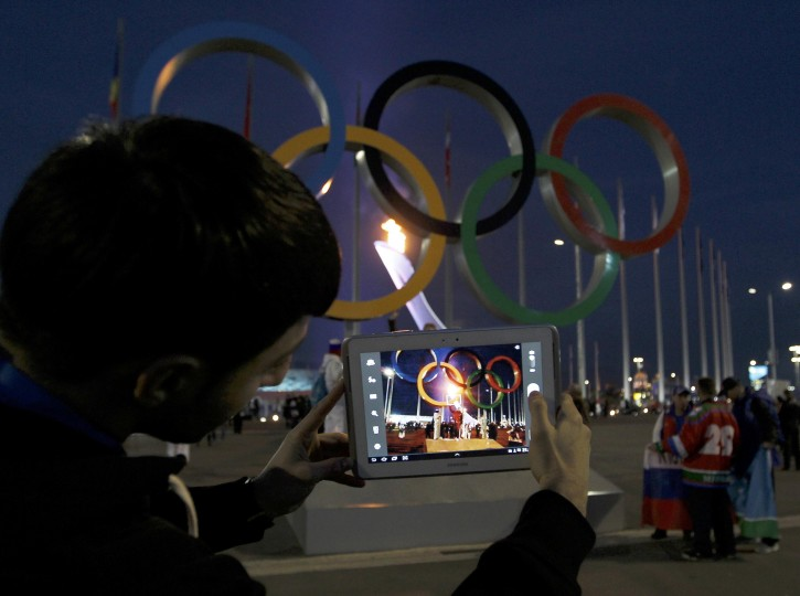 A man takes a picture of a set of Olympic rings on the Olympic Park at the 2014 Sochi Winter Olympics, February 14, 2014. REUTERS/Gary Hershorn