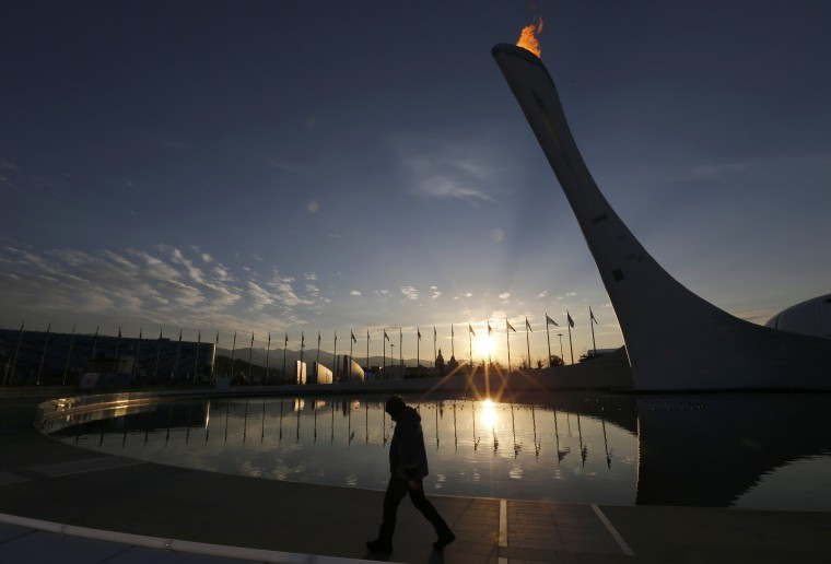 A workman walks past the cauldron as the sun rises on the Olympic Park at the Sochi 2014 Winter Olympics, February 15, 2014. REUTERS/Gary Hershorn