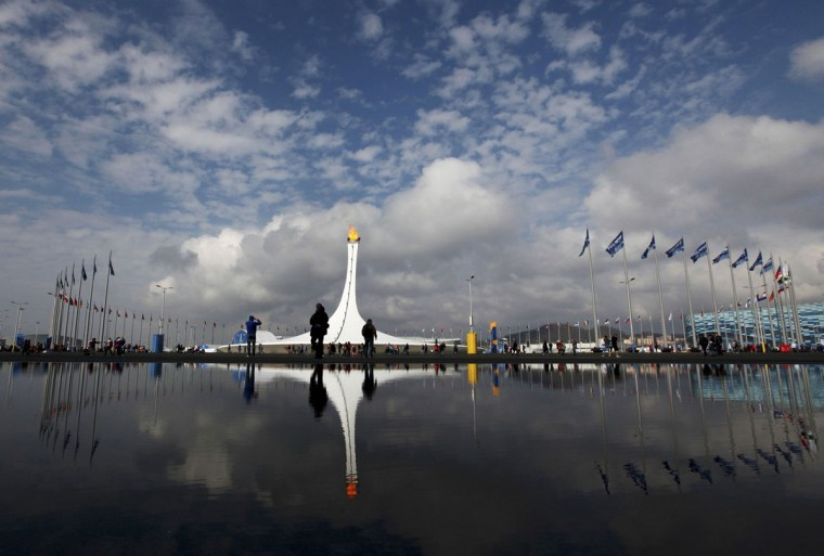 People walk past the cauldron as it is reflected in a puddle on the Olympic Park at the 2014 Sochi Winter Olympics, February 17, 2014. (Gary Hershorn/Reuters)