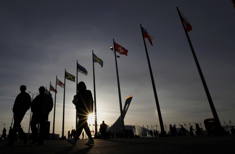 People walk through the medals plaza as the sun sets behind the cauldron on the Olympic Park at the 2014 Sochi Winter Olympics, February 19, 2014. (REUTERS/Gary Hershorn)