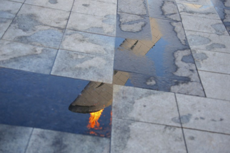 The Olympic flame is reflected in a puddle at the Olympic Park during the 2014 Sochi Winter Olympics, February 21, 2014. (REUTERS/Eric Gaillard)