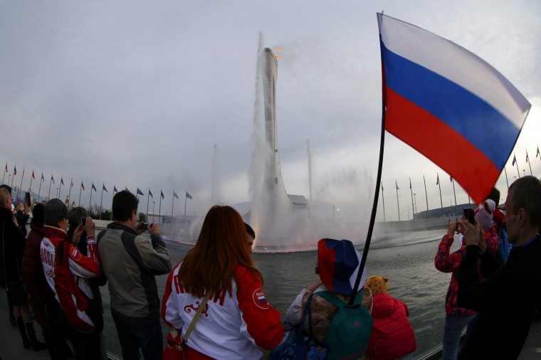 Visitors look at the water fountain and the Olympic flame at the Olympic Park during the 2014 Sochi Winter Olympics February 22, 2014. (REUTERS/Brian Snyder)