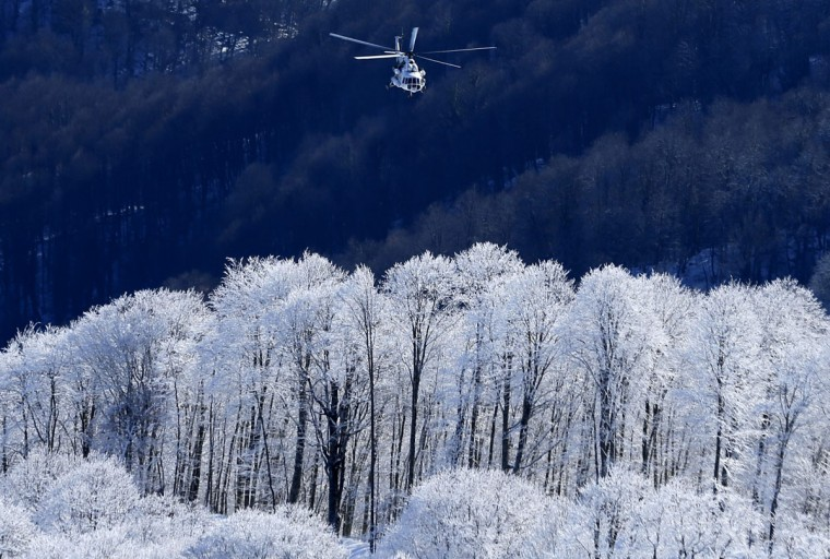 A helicopter makes its way up the mountain in Rosa Khutor as preparations continue for the 2014 Sochi Winter Olympics February 1, 2014. REUTERS/Mike Blake