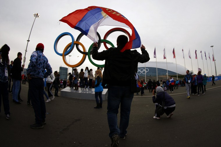 A man carries the Russian flag past the Olympic rings at the Olympic Park during the 2014 Sochi Winter Olympics February 22, 2014. (REUTERS/Brian Snyder)