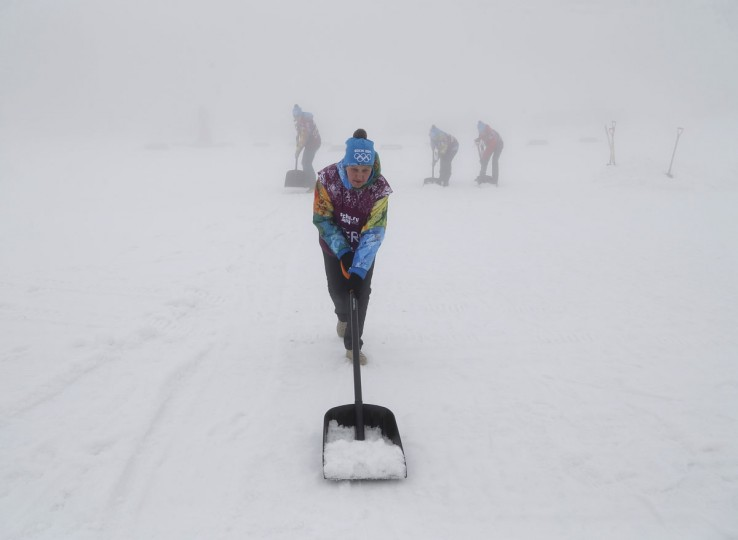Workers shovel snow in thick fog at the Laura Cross Country Ski and Biathlon Center at the Sochi 2014 Winter Olympic Games, February 17, 2014. Organisers of the Sochi Olympics defied the odds when they battled unusually warm temperatures for a week, but they were helpless against a winter fog that caused events to be postponed on Monday. The men's biathlon 15km mass start was called off for a second straight day due to thick fog. (Stefan Wermuth/Reuters)