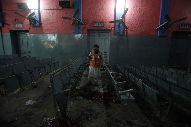 A rescue worker collects evidence at a cinema house, the site of explosions, in Peshawar, Pakistan, February 2, 2014. At least three people were killed and more than 30 others injured on Sunday night in two explosions at the cinema house, Superintendent of Police Muhammad Faisal Mukhtar confirmed in local media. (Fayaz Aziz/Reuters)