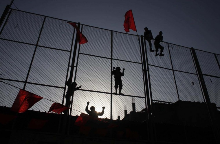 Palestinian boys climb a fence to watch a rally marking the 45th anniversary of the founding of the Democratic Front for the Liberation of Palestine (DFLP), in Rafah in the southern Gaza Strip February 24, 2014. (Reuters/Suhaib Salem)
