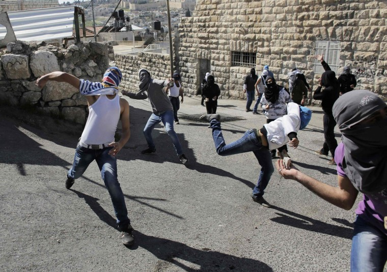 Palestinian protesters throw stones towards Israeli policemen during clashes in the Arab east Jerusalem neighbourhood of Ras al-Amud February 28, 2014. Three Palestinian protesters were detained on Friday during the clashes after they threw stones towards Israeli policemen, a police spokesman said. Israeli security forces were on high alert on Friday ahead of prayers in the Old City of Jerusalem, placing an age limit on Palestinian men wanting to enter the Old City, allowing only males above the age of 50 to enter. The tension comes after an attempt earlier in the week by an Israeli right-wing member of parliament to introduce a bill that calls for the application of Israeli sovereignty over the al-Aqsa mosque compound, located in the Old City. (REUTERS/Ammar Awad)