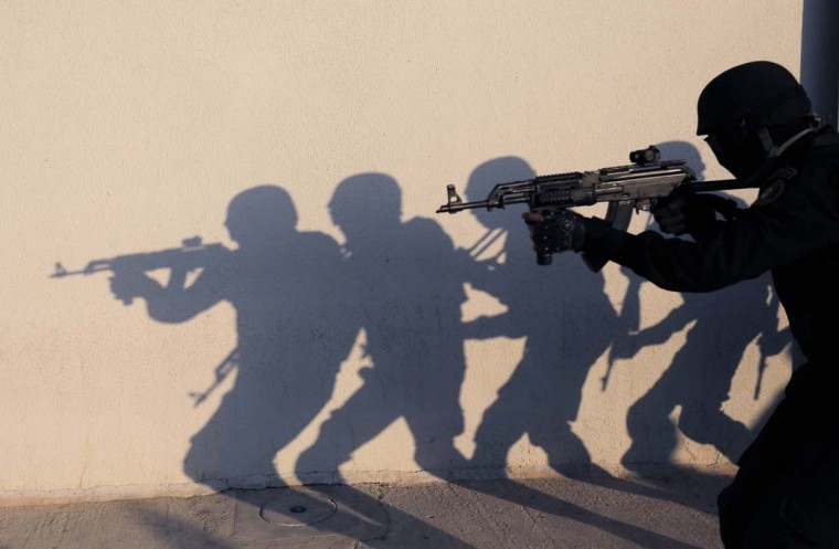 Members of the Palestinian security forces are silhouetted against a wall as they take part in a training session in the West Bank city of Jericho February 10, 2014. (Ammar Awad/Reuters)