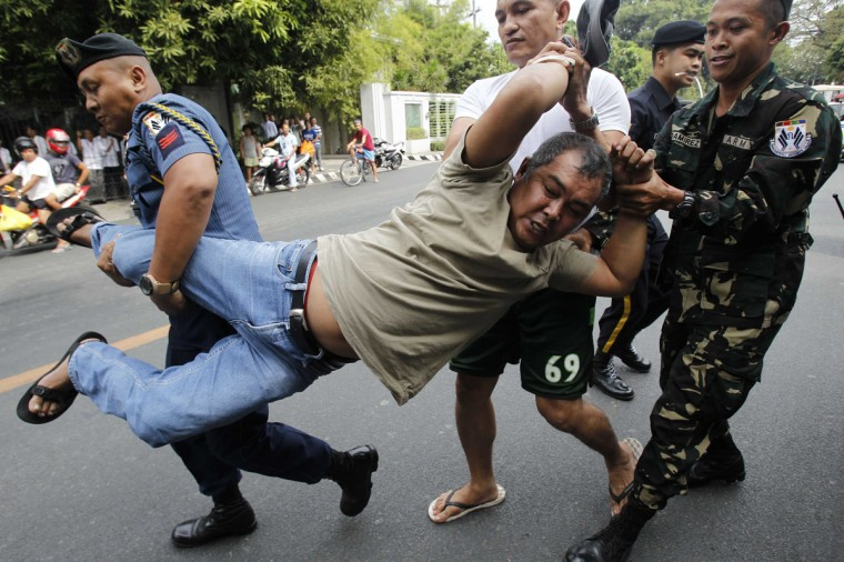 Members of the Presidential Security Group (PSG) detain a farmer activist during a protest near the Malacanang Presidential Palace in Manila February 11, 2014. The farmers are calling for President Benigno Aquino to fully implement the land acquisition and distribution component of the Comprehensive Agrarian Reform Program (CARP), according to local media. (Romeo Ranoco/Reuters)