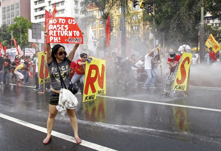 A protester stands with a placard as fellow anti-U.S. demonstrators are sprayed with water from a water canon by Philippines' Bureau of Fire Protection during a clash with riot policemen near the U.S. embassy in Manila February 25, 2014. About a hundred leftist activists tried to force their way to the U.S. embassy in Manila on Tuesday during a series of demonstrations ahead of U.S. President Barack Obama's visit to the Philippines in April, local media reported. (Romeo Ranoco /Reuters)