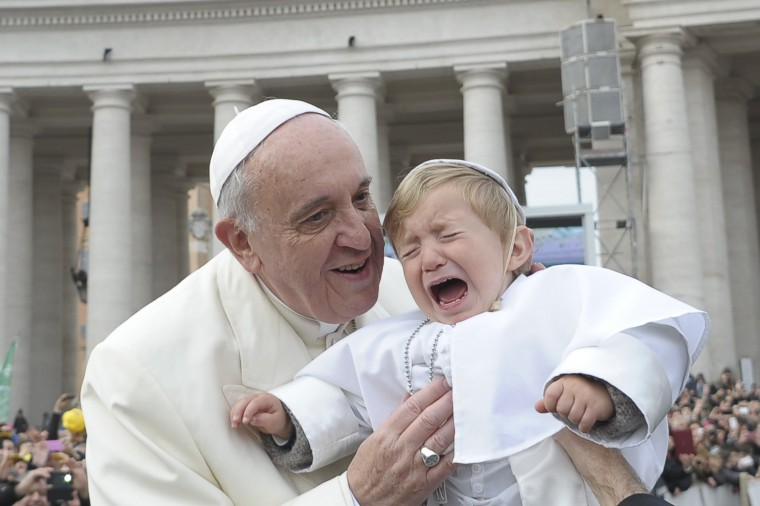 Pope Francis blesses a baby dressed as the Pope as he arrives to lead his Wednesday general audience at the Vatican February 26, 2014. (REUTERS/Osservatore Romano)