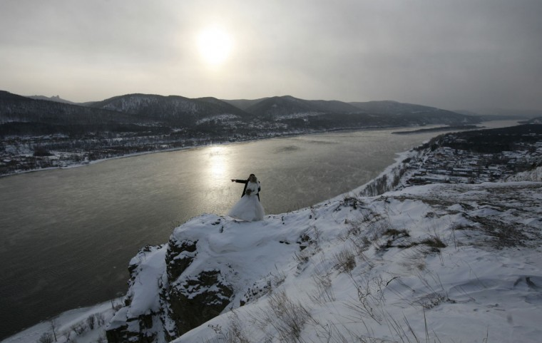 A newly married couple stand on a snow covered rock over the Yenisei River at about minus 25 degrees Celsius (minus 13 Fahrenheit) in a suburb of Russia's Siberian city of Krasnoyarsk, February 1, 2014. REUTERS/Ilya Naymushin