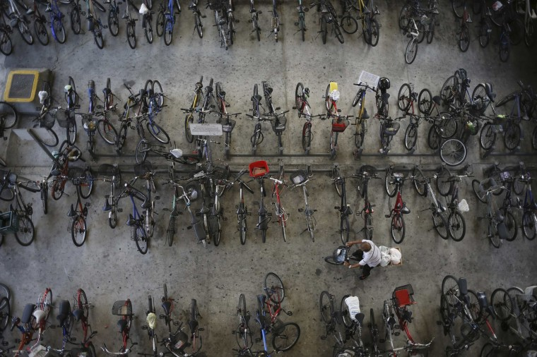 A man rides off with his bicycle outside a train station in Singapore February 28, 2014. (REUTERS/Edgar Su)