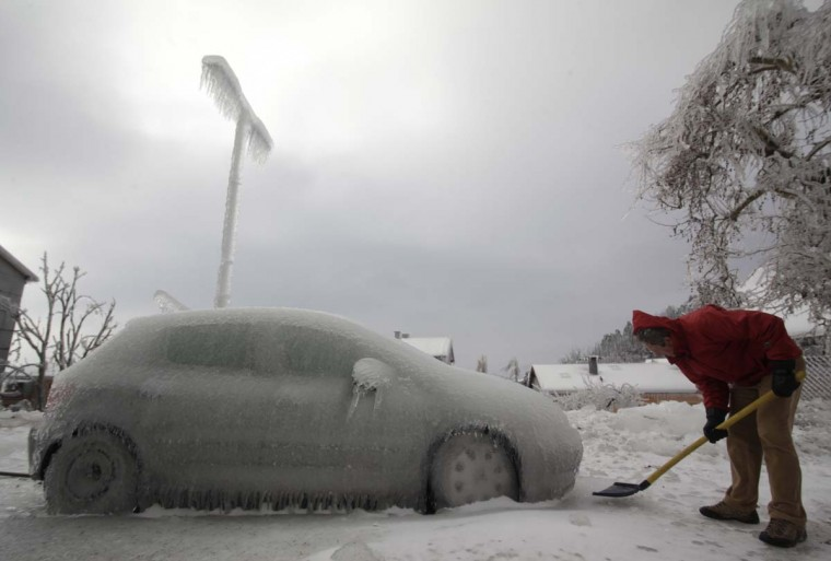 A man shovels ice next to ice-covered car in Postojna February 3, 2014. A quarter of households in Slovenia were left without electricity on Monday after a weekend of blizzards and very low temperatures wreaked havoc on power lines and roads, the national STA news agency reported. (Srdjan Zivulovic/Reuters)