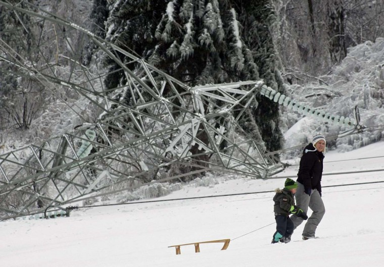 A women with child drags a sledge next to a fallen pillar of the main power lines in Strmca February 3, 2014. A quarter of households in Slovenia were left without electricity on Monday after a weekend of blizzards and very low temperatures wreaked havoc on power lines and roads, the national STA news agency reported. (Srdjan Zivulovic/Reuters)