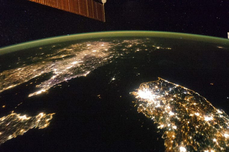 A NASA image released on February 24, 2014 shows a photo taken by the Expedition 38 crew aboard the International Space Station (ISS) on January 30, 2014 of the night view of the Korean Peninsula, and North Korea in the middle is almost completely dark compared to neighboring South Korea (bottom right) and China (top left). The photograph was cropped and enhanced to improve contrast, and lens artifacts have been removed at source. (NASA/Reuters)