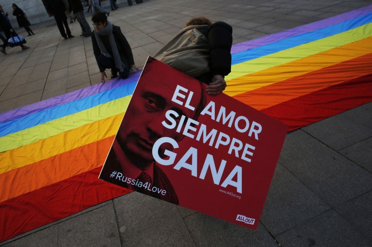 "A demonstrator helps display a rainbow flag as she holds a placard showing Russian President Vladimir Putin next to the words ""Love always wins"" at the start of a protest in Madrid against Russia's anti-gay laws ahead of the Sochi 2014 Olympic Games (Susana Vera/Reuters)"