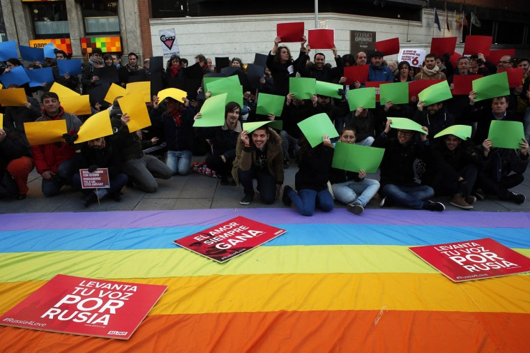 Demonstrators pose with the pieces of paper in the colors of the Olympic rings during a protest in Madrid against Russia's anti-gay laws ahead of the Sochi 2014 Olympic Games February 5, 2014. (Susana Vera/Reuters)