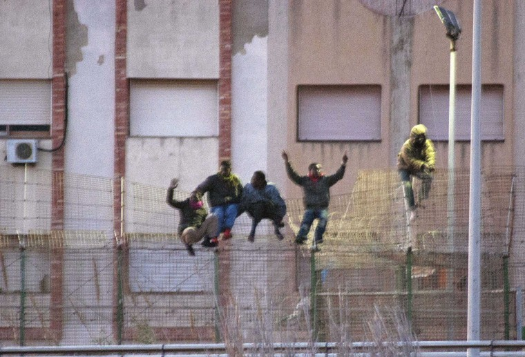 Immigrants scale over a border fence separating Spain's north African enclave Melilla from neighboring Morocco February 28, 2014. Over 200 immigrants entered Melilla through the Beni-Enzar border crossing point, according to Spain's Interior Ministry. (REUTERS/Jesus Blasco de Avellaneda)