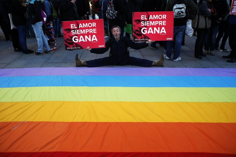 "A demonstrator poses with banners showing Russian President Vladimir Putin next to the words ""Love always wins"" during a protest in Madrid against Russia's anti-gay laws ahead of the Sochi 2014 Olympic Games February 5, 2014. (Susana Vera/Reuters)"
