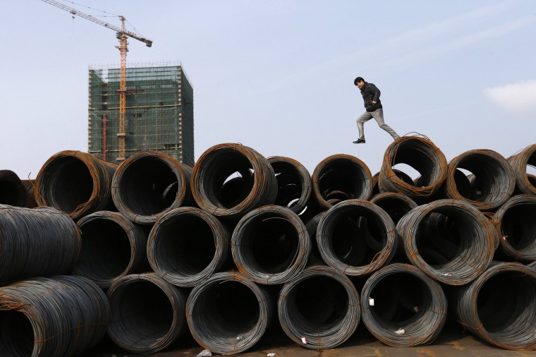 A customer jumps on piles of steel coils at a steel market in Jiaxing, Zhejiang province February 21, 2014. Global steel production fell slightly in January as the Chinese New Year holiday slowed industrial activity in the top steel producing country and as steelmakers in China and elsewhere responded to depressed demand and softer prices. (REUTERS/William Hong)