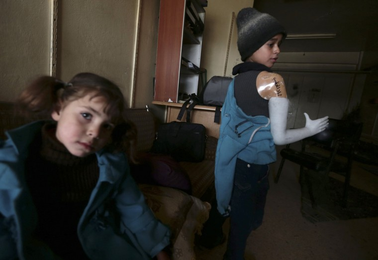 Eyad (R), a 12 year-old boy who lost his arm during shelling by forces loyal to Syria's President Bashar al-Assad, tries on a prosthetic arm at Duma Charity Foundation for Prosthesis in the Duma neighborhood in Damascus. The centre produces prostheses from different materials, including remnants of weapons, plastic mannequins and water barrels, and offer the devices to people who have lost their limbs during the war. (Bassam Khabieh/Reuters)