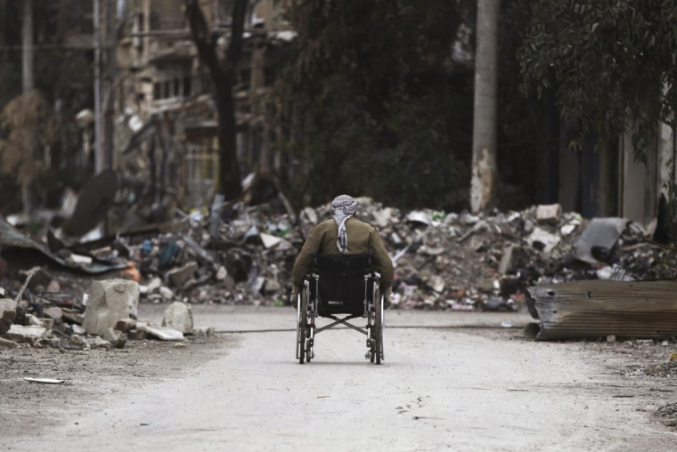 A man wheels himself on a wheelchair along a damaged street covered with debris in Deir al-Zor, eastern Syria February 3, 2014. Picture taken February 3, 2014. (Khalil Ashawi/Reuters)