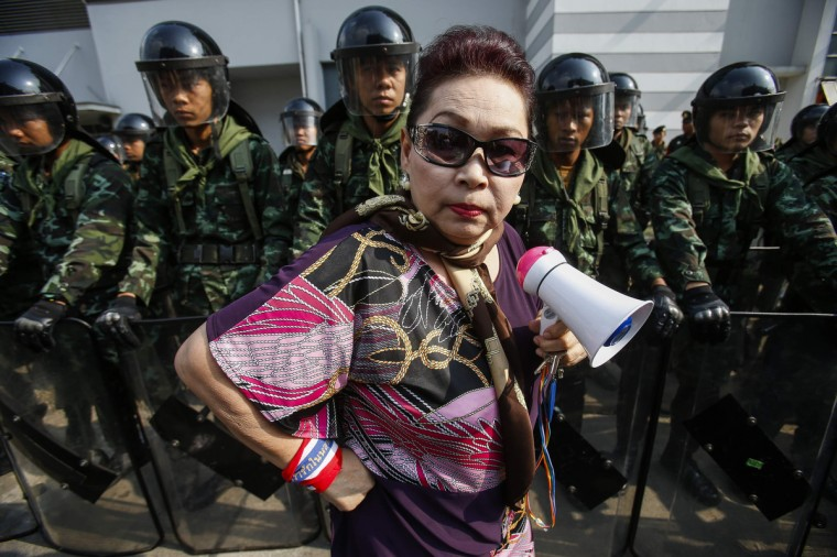An anti-government protester stands near Thai soldiers guarding a Defence Ministry compound, which is serving as a temporary office for Thai Prime Minister Yingluck Shinawatra, in north Bangkok. Protesters seeking to oust Yingluck rallied at her temporary office on Wednesday, but the premier stayed away from the potential flashpoint a day after five people were killed in gunbattles in Bangkok. (Athit Perawongmetha/Reuters)