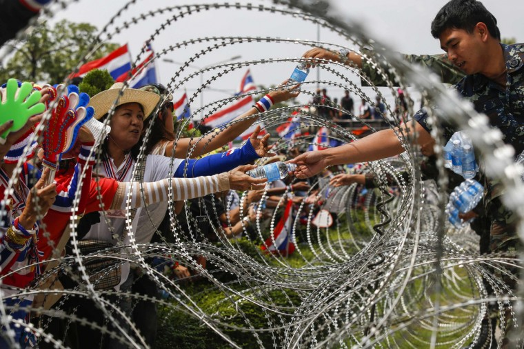 Thai soldiers hand out bottles of water to anti-government protesters through a barbed-wire fence at a Defence Ministry compound serving as a temporary office for Thai Prime Minister Yingluck Shinawatra in north Bangkok. Protesters seeking to oust Yingluck rallied at her temporary office on Wednesday, but the premier stayed away from the potential flashpoint a day after five people were killed in gunbattles in Bangkok. (Athit Perawongmetha/Reuters)
