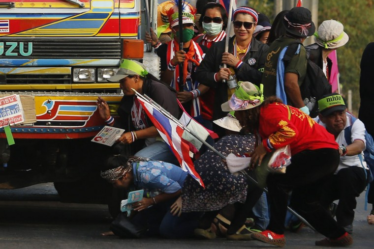 Anti-government protesters take cover behind a truck during a gunfight between supporters and opponents of Thailand's government near Laksi district office in Bangkok February 1, 2014. Dozens of gunshots and at least two explosions raised tension amid anti-government protests in Thailand's capital on Saturday, a day ahead of a general election seen as incapable of restoring stability in the deeply polarised country. REUTERS/Damir Sagolj