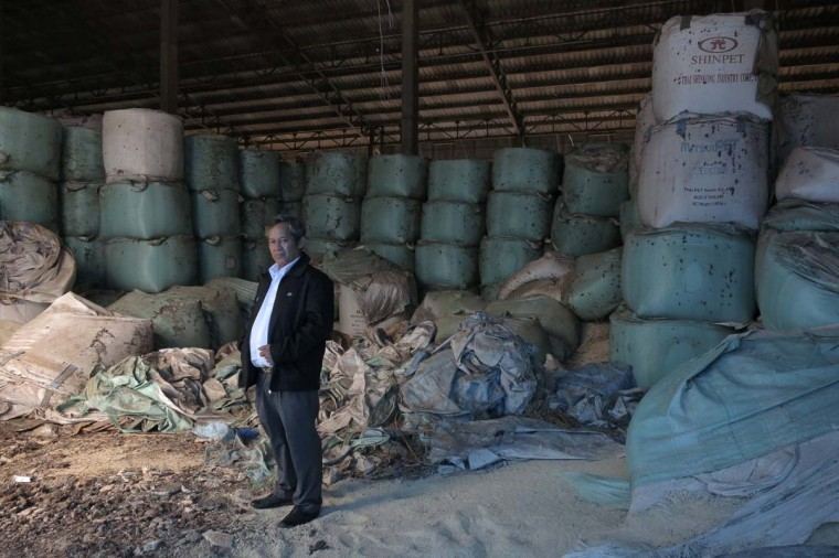 Kittisak Ratanawarahal, chairman of the Northern Farmers Network, stands in a warehouse of rotten rice abandoned ten years ago in Phichit province under a price-support scheme by then-prime minister Thaksin Shinawatra February 6, 2014. Thaksin's sister Yingluck Shinawatra is now in power and under attack for what Kittisak and other critics say is another wasteful and corrupt rice subsidy policy. Thailand's anti-corruption body said on Tuesday it had filed charges against Yingluck relating to irregularities in the government's rice-buying scheme, and it summoned her to appear to face the charges on February 27. Kittisak represents 50,000 farmers, many of whom still wait to be paid by the government for rice they have delivered. Photo taken February 6, 2014. || Credit: Andrew R.C. Marshall - Reuters