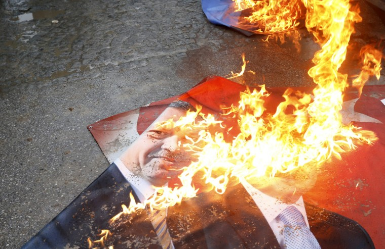 A portrait of Turkey's Prime Minister Tayyip Erdogan burns during a demonstration against the opening of a new road include a part of the Middle East Technical University campus in Ankara February 25, 2014. Erdogan opened the road across the Middle East Technical University campus and uprooting a large number of trees in the area in Ankara on Tuesday. (Umit Bektas/Reuters)