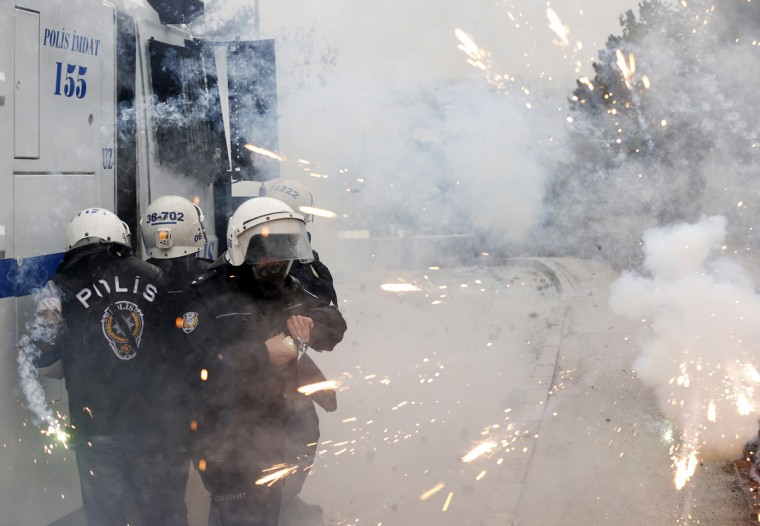 Riot police take cover as protesters use fireworks against them during a demonstration against the opening of a new road including a part of the Middle East Technical University campus in Ankara February 25, 2014. Erdogan opened the road across the Middle East Technical University campus and uprooting a large number of trees in the area in Ankara on Tuesday. (Umit Bektas/Reuters)